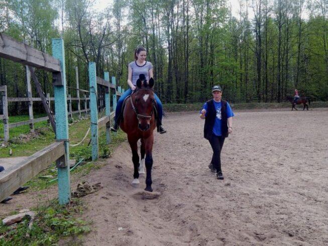 Девушка катается на лошади с инструктором