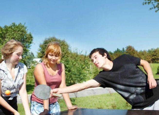 Парень и девушки играют в настольный теннис